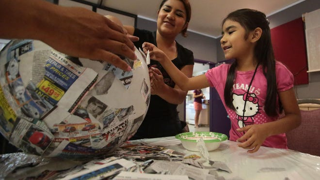 Jade Guidos, 7, and Luisa Carranza, of Cathedral City, make paper mache masks during an art party at the Cathedral Center on Saturday. The masks would be worn by children in a parade as part of the Taste of Jalisco Festival in November.