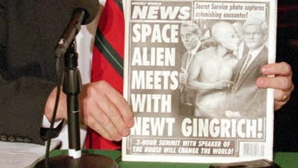 "House Speaker Newt Gingrich of Georgia holds a a copy of the Weekly World News with a headline ""Space Alien meets with Newt Gingrich"" during his daily Capitol Hill news conference Tuesday, Feb. 21, 1995. Earlier, Gingrich assailed President Clinton for opposing the balanced budget amendment and labeled him the key obstacle to turning the Republicans ""Contract with America"" into law."