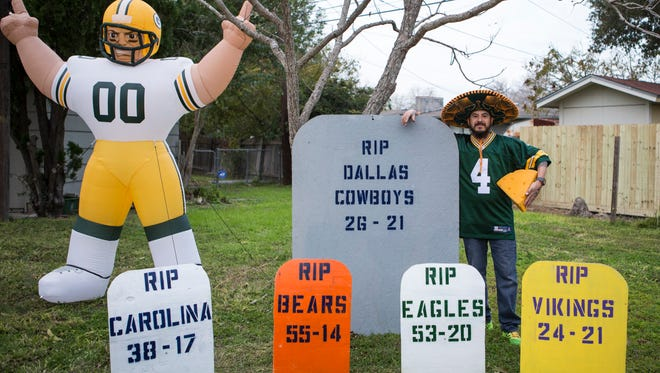 """Marcos Flores stands next to the large Dallas Cowboys gravestone inside his """"Green Bay Boneyard"""" in Corpus Christi."""