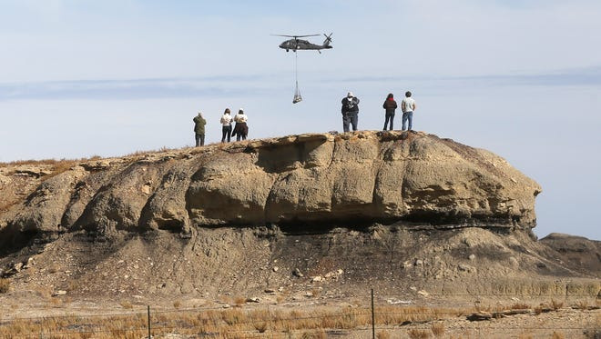 A group of people watches on Oct. 29 as a Black Hawk helicopter carries a piece of an adult Pentaceratops out of the Bisti/De-Na-Zin Wilderness south of Farmington.