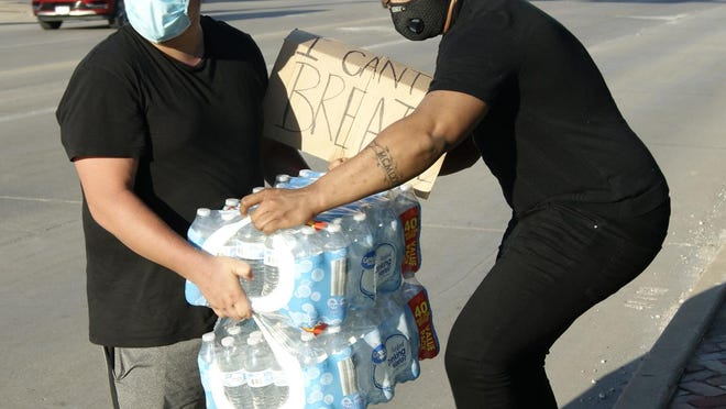 Firday, June 5, 2020, approx. 6 p.m.: A newly-joined protester crossed the street with two cases of water before another protester helped carry them to the park's gates.