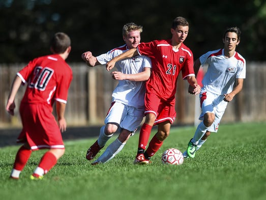 Liberty Common's Sam Huggins, center, fights for the ball during the soccer game against Colorado Academy Wednesday, September 3, 2014, in Fort Collins, CO.