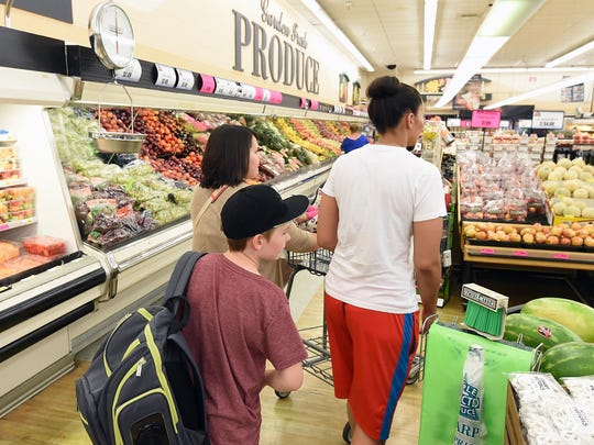 Sarah Reynolds, left, and Nikki Mitchell, along with their son, shop at a local grocery store.