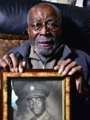 Austin Powlis, 92, at his Teaneck home with a photo from his days in the service.
