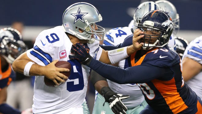 Dallas Cowboys quarterback Tony Romo (9) is sacked in the fourth quarter by Denver Broncos defensive end Shaun Phillips (90) at AT&T Stadium.