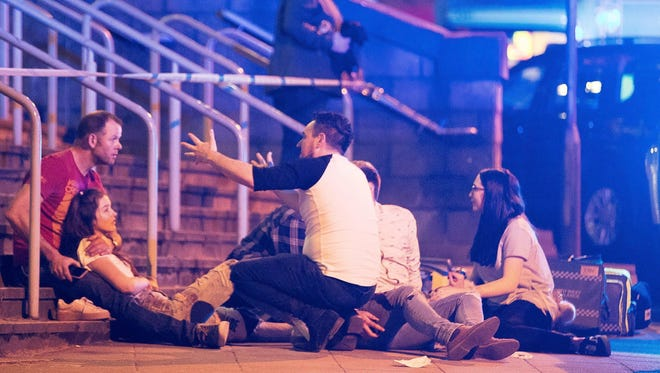 Police and bystanders are seen near the Manchester Arena after reports of an explosion at the Ariana Grande concert, Monday.