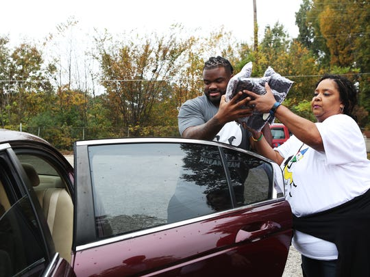 November 7, 2017 - Dontari Poe, a former University of Memphis football player and current defensive tackle for the Atlanta Falcons, and Tammi Redmond, a member of the Order of the Eastern Star, Hannah Number 20 of Southaven, MS, distribute groceries to 200 needy families at The Healing Center, at 3885 Tchulahoma Road, on Tuesday. The event was possible through Poe's foundation, Poeman's Dream Foundation, and the Memphis Food Bank.