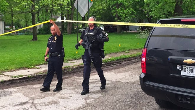 Crime scene tape is lifted for a SWAT officer approaching the killing scene on Hamilton Avenue on Thursday.