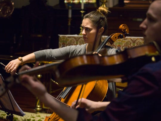 Cellist Madeline Fayette, center, practices alongside