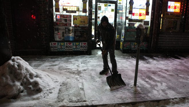 Rocky Patel clears the sidewalk of snow in front of his business, Dan's Tobacco on Yonkers Avenue in Yonkers, during the early morning snowfall on Feb. 17.