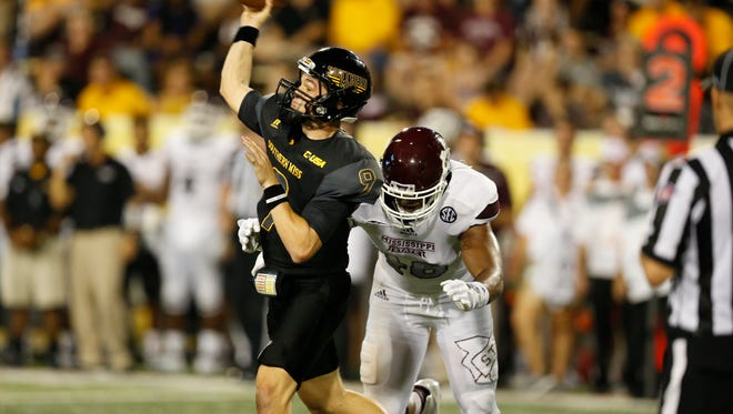Southern Mississippi quarterback Nick Mullens (9) passes as Mississippi State defensive lineman Ryan Brown (48) rushes during the second half of an NCAA college football game at M.M. Roberts Stadium in Hattiesburg Miss., Saturday, Sept. 5, 2015. Mississippi State won 34-16. (AP Photo/Rogelio V. Solis)