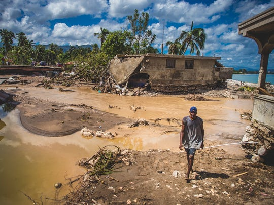 A man walks across flooded countryside in Nippes, Haiti.