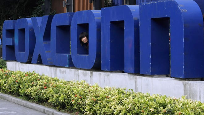 In this May 27, 2010, file photo, a worker looks out through the logo at the entrance of the Foxconn complex in the southern Chinese city of Shenzhen.