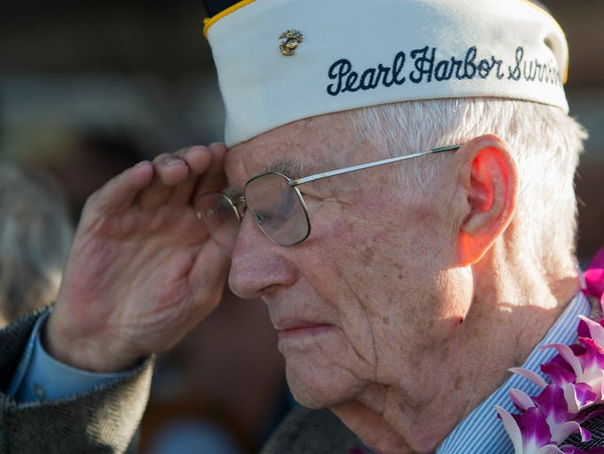 Pearl Harbor survivor John Stevens salutes the flag at the start of a ceremony commemorating the 72nd anniversary of the attack on Pearl Harbor in Honolulu.