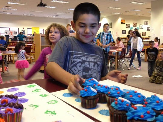 A child chose a cupcake after winning during a cakewalk at Loving's birthday celebration for Dr. Seuss.