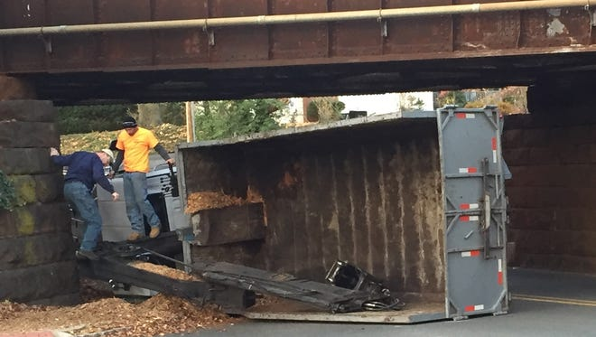 A man helping the driver out of an overturned truck below the Short Hills train station overpass.
