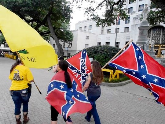People waving confederate flags walk by the confederate monument  during the GULF Coast Patriot Network 'Rally To Be United As One' event Saturday morning at the Caddo Parish Courthouse.