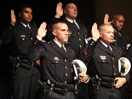 Craig Graening (foreground left) and other members of the 105th class of Cincinnati Police recruits were sworn in at their graduation ceremony in June at Cincinnati Christian University in East Price Hill.