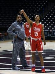 Winston Garland watches as his son Darius shoots a