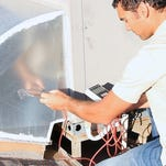 Alex Williams checks static pressure during a home energy audit.