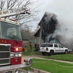 Battle Creek firefighters outside a home heavily damaged by fire at 39 Walnut Ave. Saturday.