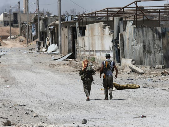 U.S.-backed Syrian Democratic Forces fighters walk