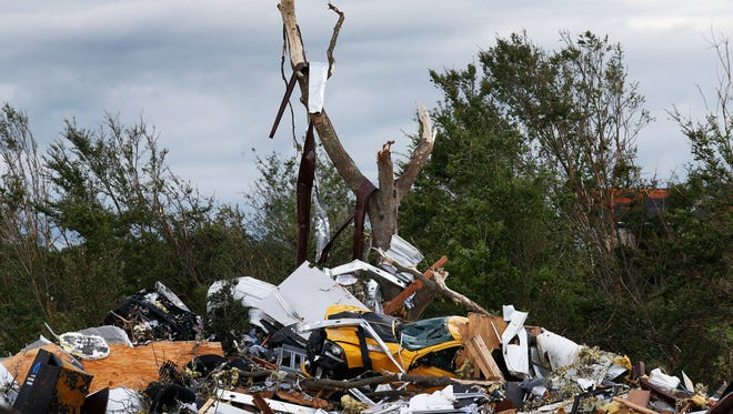 Cars and damaged material is seen piled up at a local car dealership that was destroyed when a large tornado hit the area near Canton, Texas on April 30, 2017.
