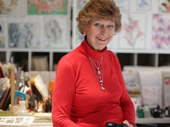 Artist Julie Dawson poses in her studio at her home