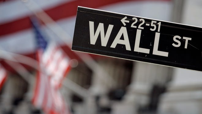 In this May 11, 2007, photo, a Wall Street sign is mounted near the flag-draped facade of the New York Stock Exchange. (AP Photo/Richard Drew, File)