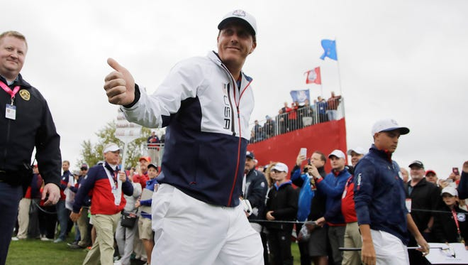 Phil Mickelson gives a thumbs up as he walks to the third hole during a practice round for the Ryder Cup golf tournament Wednesday at Hazeltine National Golf Club in Chaska, Minn.