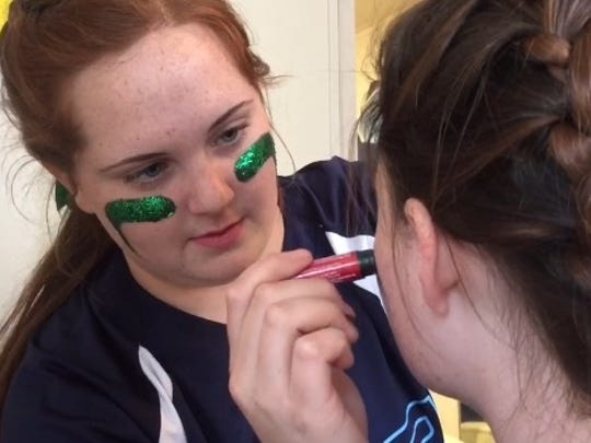 Loyola's Sarah Szwak applies eye-black on the face