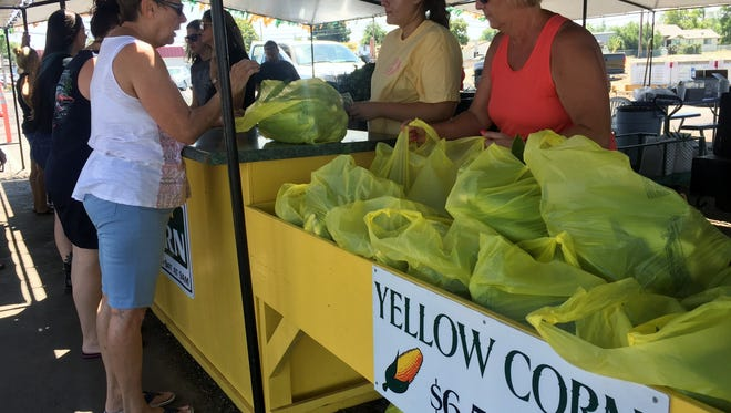 Shaylie Logan and Kim Gisler hand over bags of sweet corn to a customer, Saturday morning at the stand. Gisler Farm's sweet corn stand on 1616 W Olive Ave., Porterville is open Monday through Saturday from 9 a.m., until they sell out.