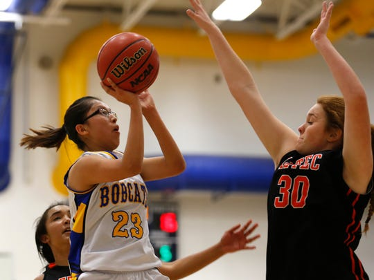 Bloomfield's Kimberyln Morgan attempts a shot while defended by Aztec's Kamrynn Phelps on Jan. 4 at Bobcat Gym in Bloomfield.