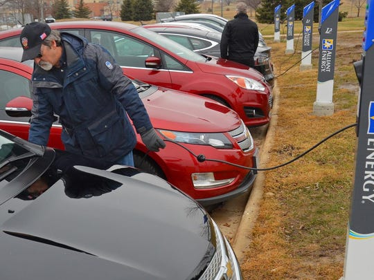 Gov. Tony Evers' budget includes funding and policies to encourage more green power and fewer carbon emissions.  An Alliant Energy employee charges a vehicle in Madison.
