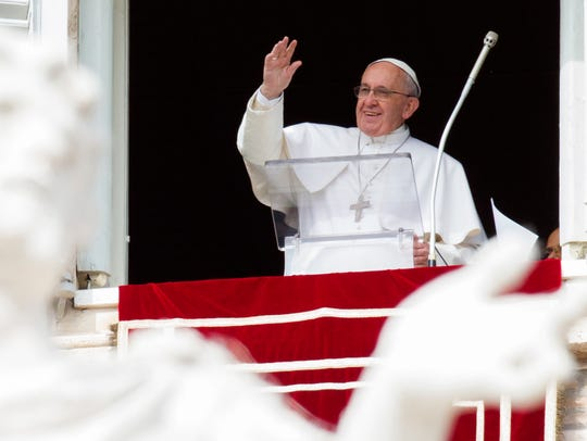 Pope Francis waves to people from his studio window