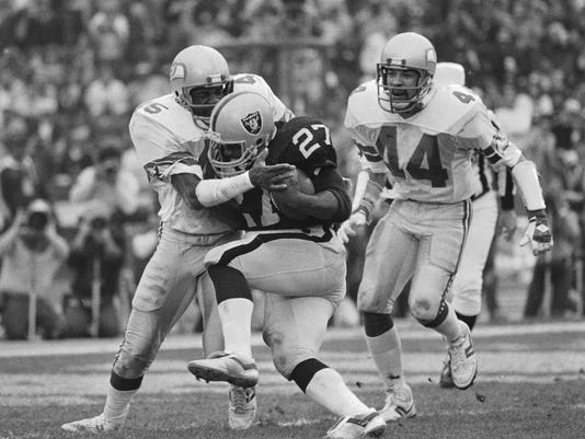 FILE - In this Jan. 8, 1984, file photo, Los Angeles Raiders running back Frank Hawkins (27) pushes his way across the goal line for his second touchdown of the day despite the defensive efforts of Seattle Seahawks' Kenny Easley during an NFL football game in Los Angeles. Thirty years after Easley walked away from football due to health issues that were the source of his disillusionment with the game, he is embracing the recognition he is finally receiving. He even dreamt of the induction the night before he found out he was bound for the Pro Football Hall of Fame. (AP Photo/File)