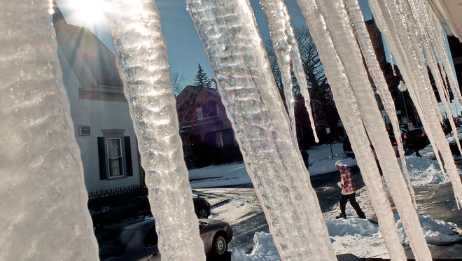 A man crosses Elm Street beyond icicles hanging from the gutter of a building Wednesday, in New Bedford, Mass.