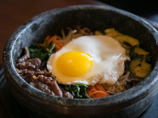 Bibimbap is a layered Korean dish with rice, vegetables, bean paste, sliced beef and a fried egg.