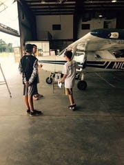 Members of Aero Camp look at a plane inside a hanger.
