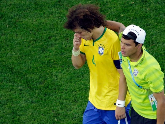 Brazil's David Luiz is consoled by teammate Thiago Silva as they walk off the pitch after the World Cup semifinal soccer match between Brazil and Germany at the Mineirao Stadium in Belo Horizonte, Brazil, Tuesday, July 8, 2014. Germany has routed host Brazil 7-1 and advanced to the final of the World Cup. (AP Photo/Felipe Dana, Pool)