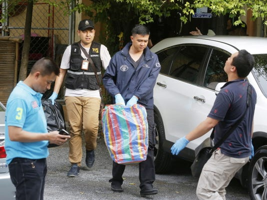 Thai policemen take evidence at an apartment on Saturday in the outskirts of Bangkok.