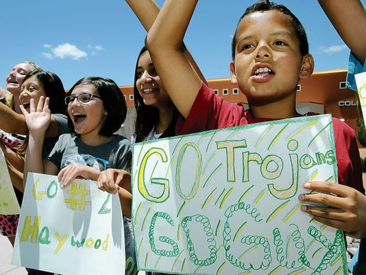 Columbia student Roman Fuentes, 11, right, holds a poster and cheers on the MHS baseball team along with his classmates.