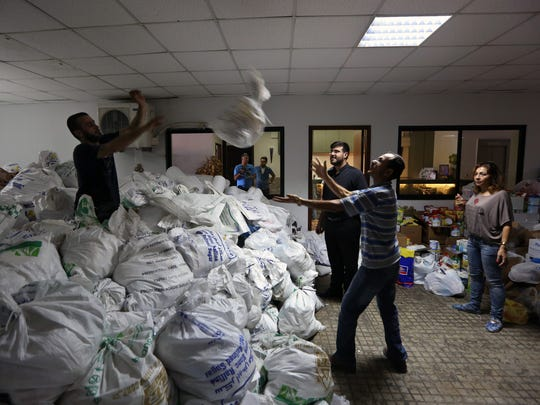 Christian volunteers distribute food and clothes to Iraqis who fled their homes in Iraq and came to Lebanon, at the Chaldean Diocese in Baabda, east of Beirut, Lebanon.