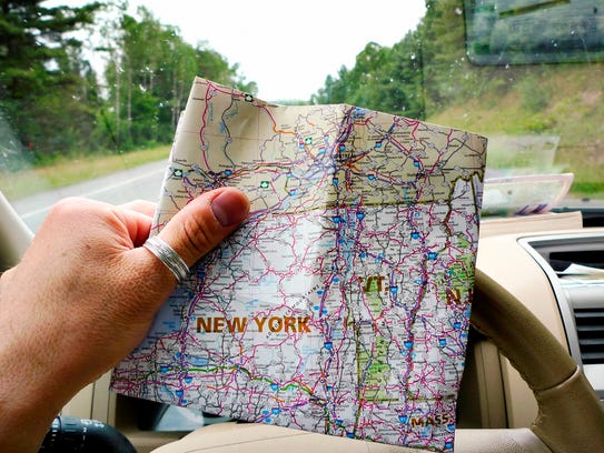Traveling man looking at map of New York in car, while