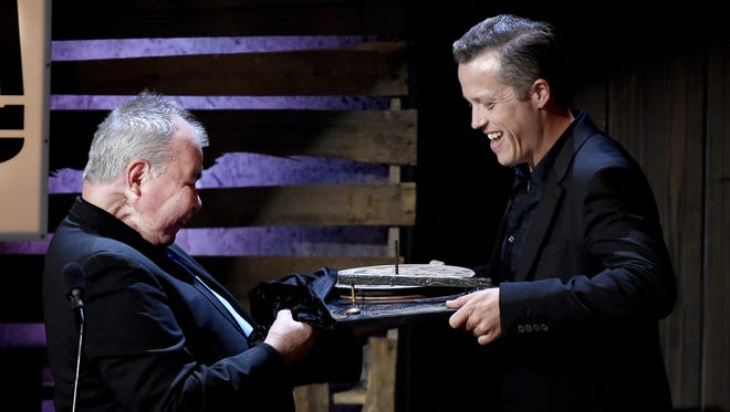 John Prine, left, presents Album of the Year to Jason Isbell during the Americana Music Honors and Awards show at Ryman Auditorium Sept. 21, 2016.