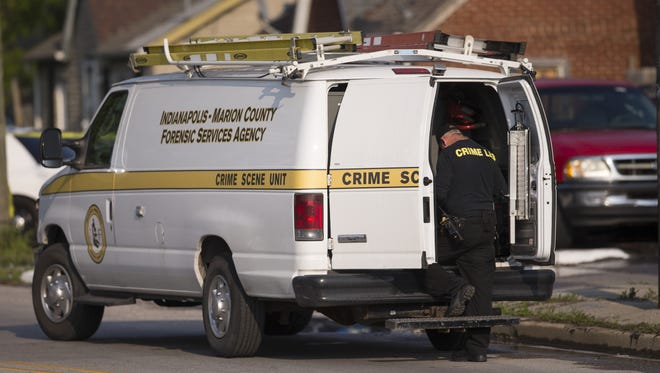 Crime scene investigators from Indianapolis Metropolitan Police Department at the scene of fatal shooting.
