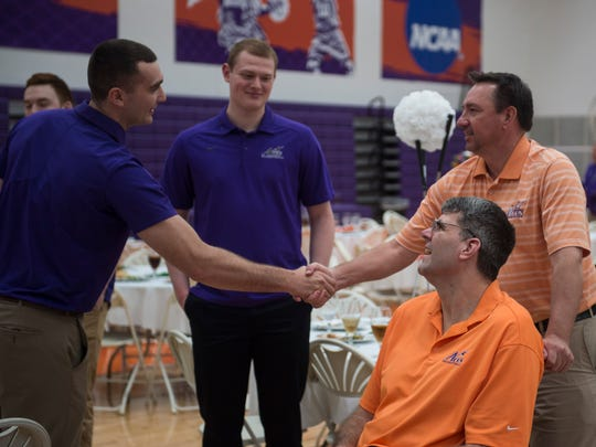 Former basketball players Blake Simmons, left, and Scott Shreffler, right, shake hands as current player Evan Kuhlman, middle left and former player Sascha Hupmann, middle right, watch on during the Lunch with the Aces at the Meeks Family Fieldhouse on Friday, April 13, 2018.