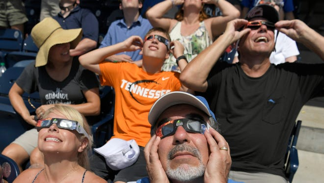 Ken Abraham and wife Lisa look up at the eclipse at the city's viewing party at First Tennessee Park Monday, Aug. 21, 2017 in Nashville, Tenn.