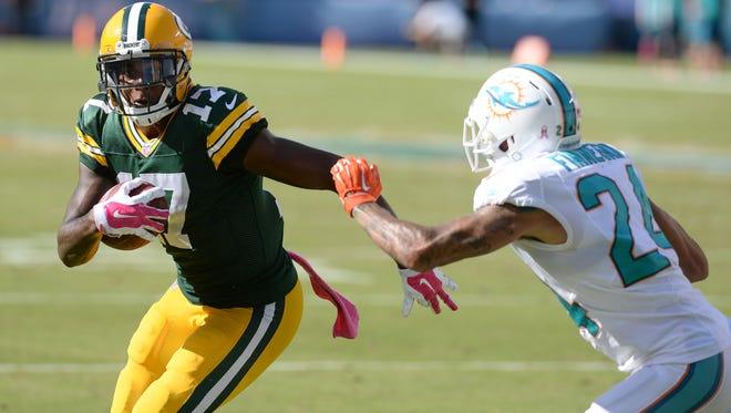 Green Bay Packers receiver Davante Adams (17) makes the catch against cornerback Cortland Finnegan (24) on a fake spike play late in the fourth quarter against the Miami Dolphins at Sun Life Stadium.