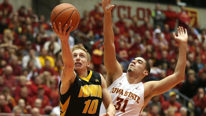 Iowa's Mike Gesell gets around Iowa State's Georges Niang for a field goal on Dec. 13, 2013, at Hilton Coliseum in Ames.